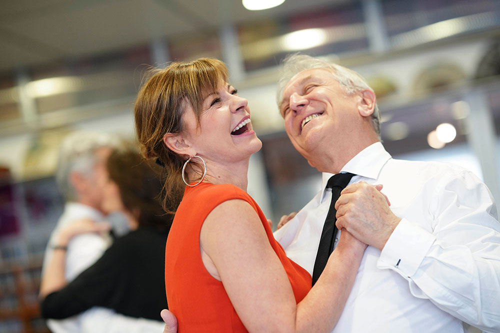 a husband in a white shirt and tie and wife in a red dress dancing together and laughing