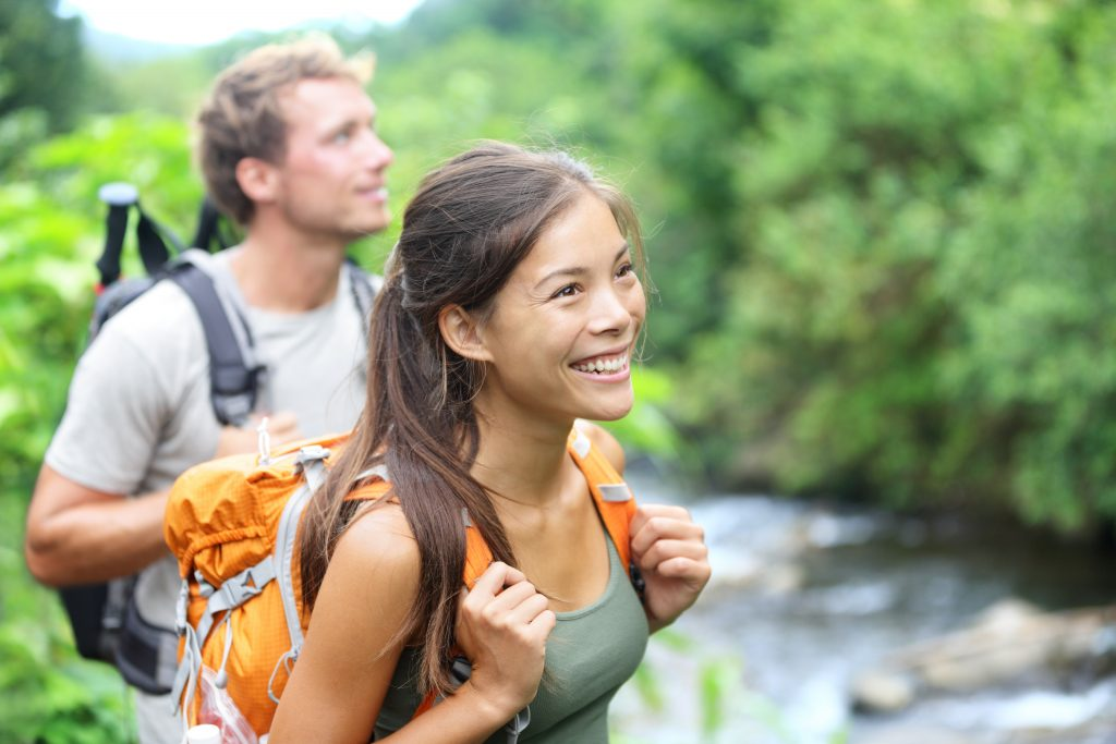 young couple hiking through the wilderness and smiling while standing in front of a river