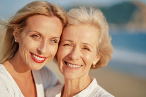 middle aged and elderly woman smiling on a beach together