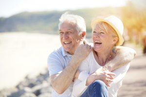 elderly couple hugging and laughing outdoors