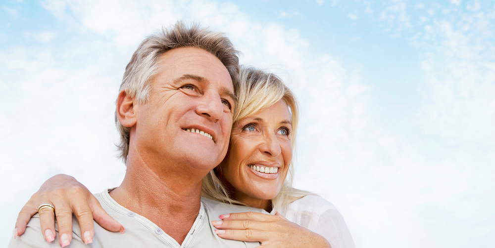happy older couple holding each other and smiling underneath a bright blue sky